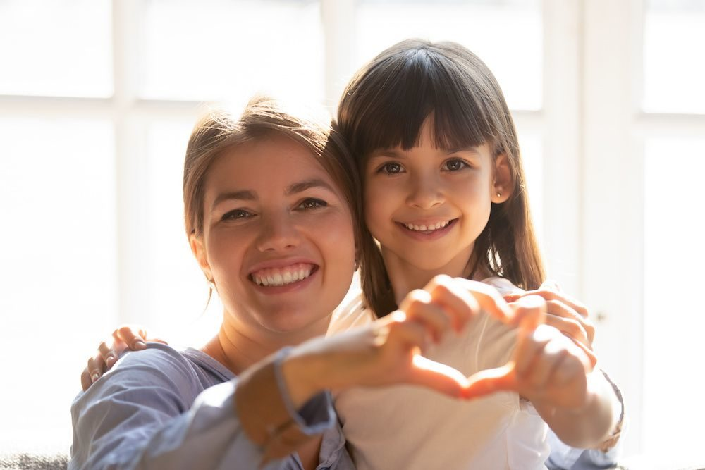Legal Service_Equitable Parent-Stepparent Custody_Mother and daughter make heart shape with hands_1000x667_C